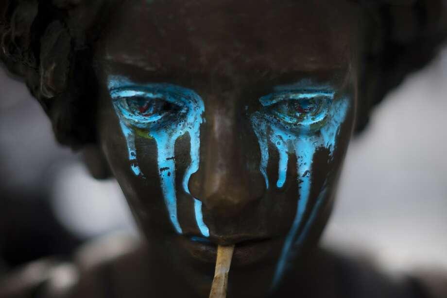 A crying shame:A vandalized statue in Madrid weeps tears of blue paint. Photo: Daniel Ochoa De Olza, Associated Press