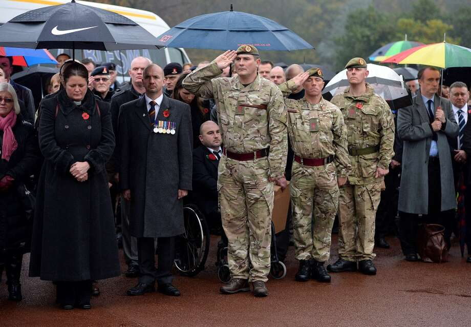Mourners stand in silence as servicemen salute during the funeral of World War II veteran Harold Percival at Lytham Park Cemetery on November 11, 2013 in Lytham St Annes, England. Hundreds of strangers attended the funeral of former RAF Bomber Command ground crew member, Harold Jellicoe Percival, following an online campaign sparked by a notice placed in a newspaper by the funeral directors. Photo: Nigel Roddis, Getty Images