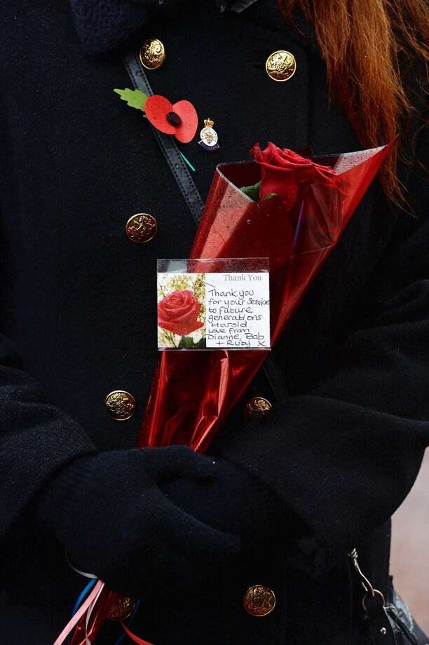 A woman holds a floral tribute during the funeral of World War II veteran Harold Percival at Lytham Park Cemetery on November 11, 2013 in Lytham St Annes, England. Hundreds of strangers attended the funeral of former RAF Bomber Command ground crew member, Harold Jellicoe Percival, following an online campaign sparked by a notice placed in a newspaper by the funeral directors. Photo: Nigel Roddis, Getty Images