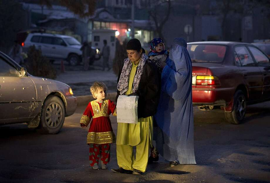 Roadside assistance needed: An Afghan family begs for money in the center of Kabul. Hundreds of Afghans compete daily for a handful of jobs 