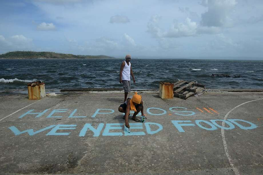 After the deluge: A hungry Filipino man paints an S.O.S. on a seaside basketball court in Tacloban, Leyte, 