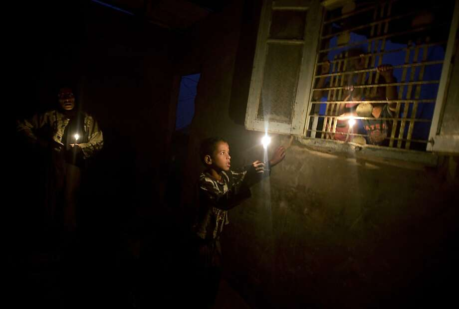 Blackout beaters: A Palestinian boy and his mother light candles during a power outage in Gaza City. Photo: Mahmud Hams, AFP/Getty Images