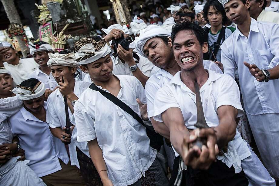 Point taken: A Balinese worshipper jabs himself with a ceremonial dagger called a keris to perform ngurek, a self-stabbing ritual at a 
