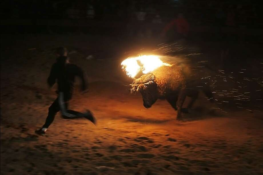 Another Spanish tradition that should be retired: A flaming bull chases a reveler in the ancient Toro de Jubilo Fire Bull Festival in Medinaceli, Spain. During the event, flammable balls are attached to the horns of a bull that is tied to a pylon. A thick layer of mud is applied to the back and face of the animal to protect it from burns. The balls are lit and the bull released, no doubt freaking out because its head is on fire. Photo: Andres Kudacki, Associated Press