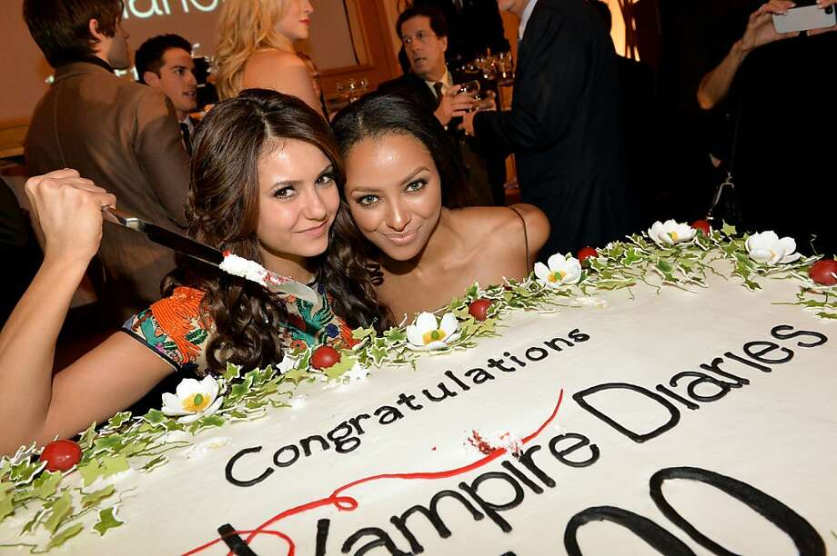 "Stick a knife in it: In Atlanta, actresses Nina Dobrev and Kat Graham take a stab at cutting the cake for ""The Vampire Diaries"" 100th Episode 