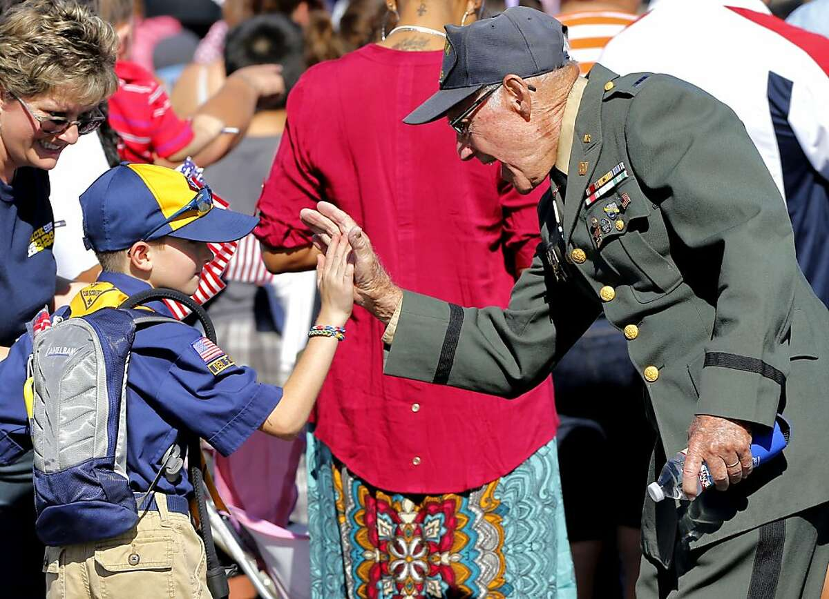 Cub Scout Carter Chase, 7, high fives WWII U.S. Army veteran Oliver Babbitts during a Veteran's Day parade, Monday, Nov. 11, 2013, in downtown Phoenix. Across the nation, Americans are commemorating the service and sacrifice of military service members this Veterans Day.