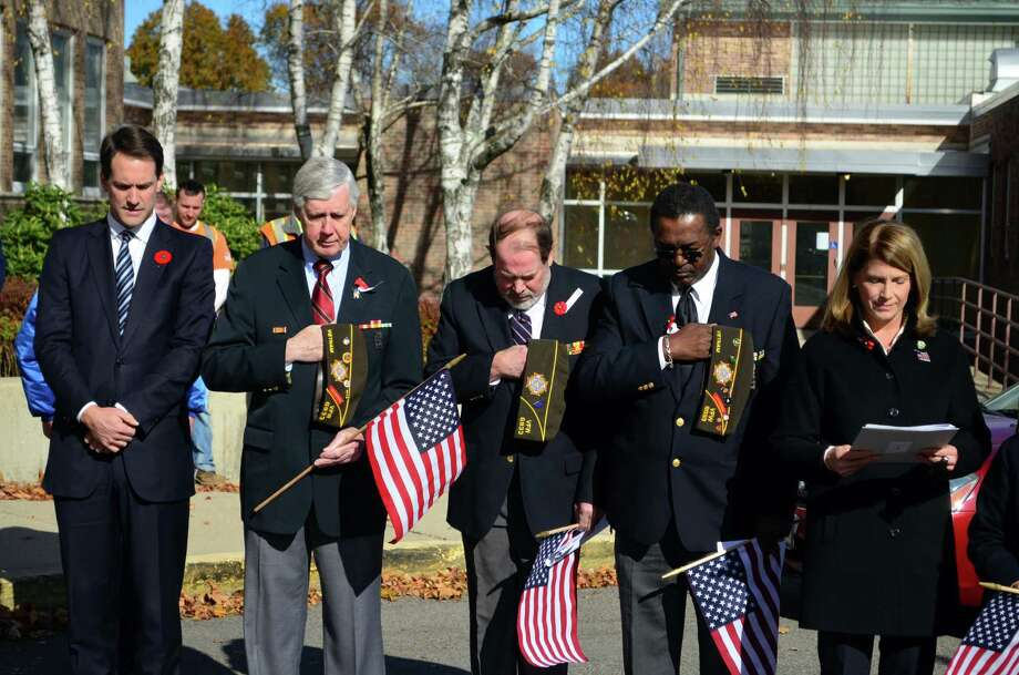 Congressman Jim Himes, along with members of the Darien Veterans of Foreign Wars and First Selectman Jayme Stevenson bow their heads in silence during the Veterans Day ceremony outside Town Hall on Monday, Nov. 11. Photo: Megan Spicer / Darien News