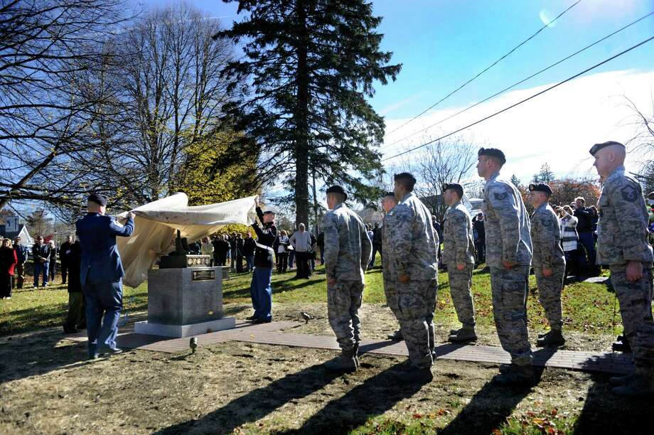 "A monument dedicated to Todd ""T.J."" Lobraico is unveiled at a Veterans Day ceremony Monday. The town of New Fairfield, Conn. recognized Veterans Day with a ceremony at Veterans Green that included the dedication of a monument honoring Staff Sgt. Todd "" T.J."" Lobraico and other town residents killed in action, Monday. Nov. 11, 2013.  Lobraico, serving in Afghanistan, died Sept. 5. Photo: Carol Kaliff / The News-Times"