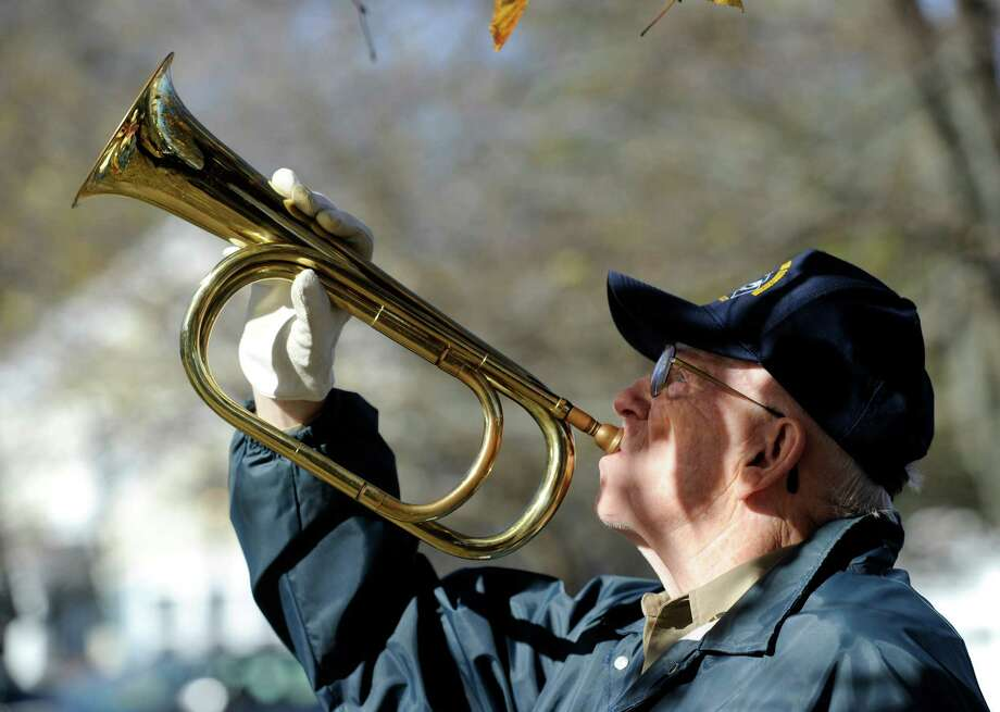 "Stanley ""Red""  Britton, 80, of Danbury, plays Taps during New Fairfield's Veterans Day Ceremony Monday. The town of New Fairfield, Conn. recognized Veterans Day with a ceremony at Veterans Green that included the dedication of a monument honoring Staff Sgt. Todd ""T.J."" Lobraico and other town residents killed in action, Monday. Nov. 11, 2013.  Lobraico, serving in Afghanistan, died Sept. 5. Photo: Carol Kaliff / The News-Times"
