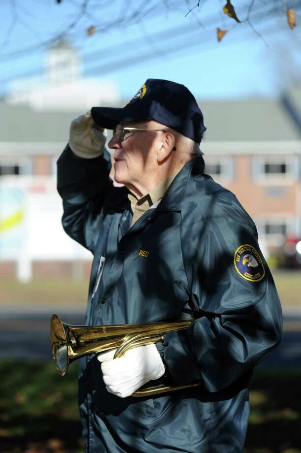 "Stanley ""Red""  Britton, 80, of Danbury, played Taps during New Fairfield's Veterans Day Ceremony Monday. The town of New Fairfield, Conn. recognized Veterans Day with a ceremony at Veterans Green that included the dedication of a monument honoring Staff Sgt. Todd ""T.J."" Lobraico and other town residents killed in action, Monday. Nov. 11, 2013.  Lobraico, serving in Afghanistan, died Sept. 5. Photo: Carol Kaliff / The News-Times"