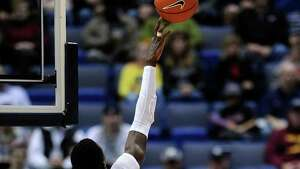 Connecticut's Amida Brimah (35) gets one of his seven blocks against Yale's Brandon Sherrod during the first half of an NCAA college basketball game, in  Hartford, Conn., on Monday, Nov. 11, 2013. Connecticut won 80-62.