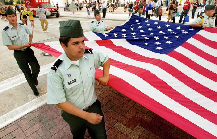 Members of the Magnolia Junior ROTC march with an American Flag during the annual City of Houston Veterans Day parade on Monday, Nov. 11, 2013, in Houston.  The celebration also included a Veterans job and health fair. Photo: J. Patric Schneider, For The Chronicle / © 2013 Houston Chronicle