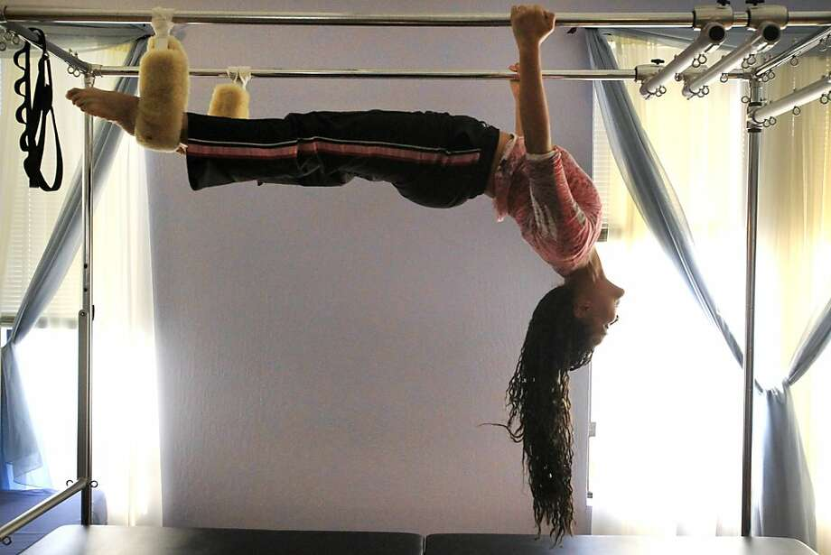 "Tonya Marie Amos demonstrates the ""Batgirl"" move on the trapeze table at Aspire Pilates Center in Concord. Photo: Leah Millis, The Chronicle"