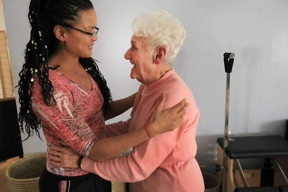 Tonya Marie Amos, left, hugs one of her clients, Lena Cirimele, 93, goodbye after demonstrating a typical workout routine with her November 7, 2013 at Aspire Pilates Center in Concord, Calif.