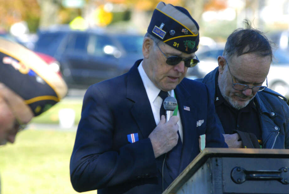 Dan Sullivan, speaking, and James Delancy of the New Milford Veterans Committee, bow their heads during the opening prayer for New Milford's Veterans Day ceremony on the south end of the Village Green in New Milford. Nov. 11, 2013 Photo: Norm Cummings / The News-Times