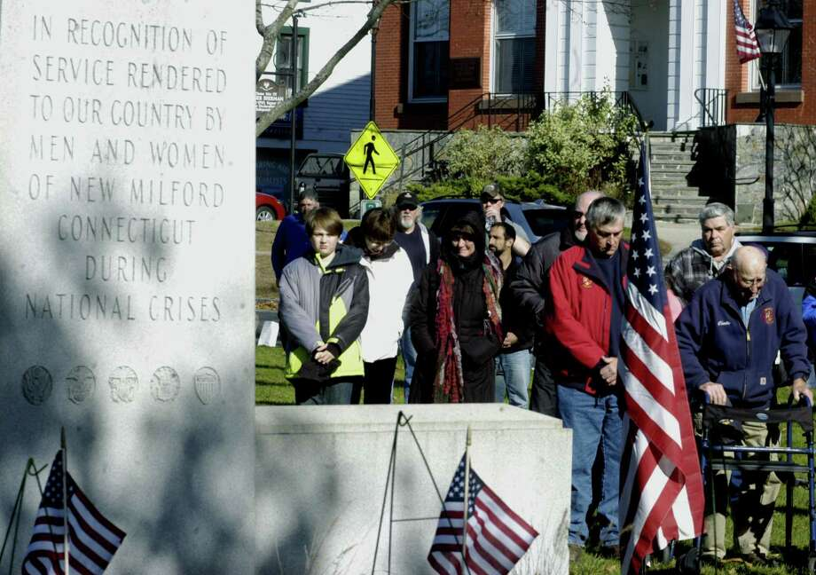 World War II veteran Charlie Aldrich, right, and his son, Fred, stand side by side as prayers are offered during  New Milford's Veterans Day ceremony on the south end of the Village Green in New Milford. Nov. 11, 2013 Photo: Norm Cummings / The News-Times