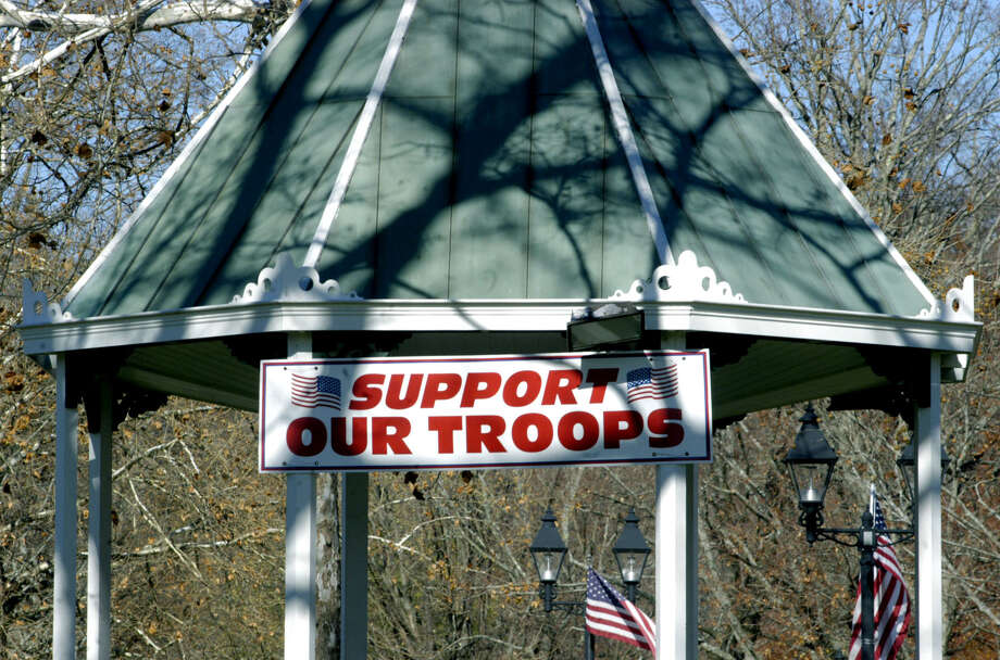 A sign hanging from the bandstand states the town's feelings about its men and women in the U.S. military service during New Milford's Veterans Day ceremony on the south end of the Village Green in New Milford. Nov. 11, 2013 Photo: Norm Cummings / The News-Times