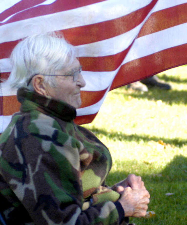 "Moments after singing ""God Bless America,"" Korean War veteran Francis Hill relaxes to the fitting backdrop of The Stars and Stripes during New Milford's Veterans Day ceremony on the south end of the Village Green in New Milford. Nov. 11, 2013 Photo: Norm Cummings / The News-Times"