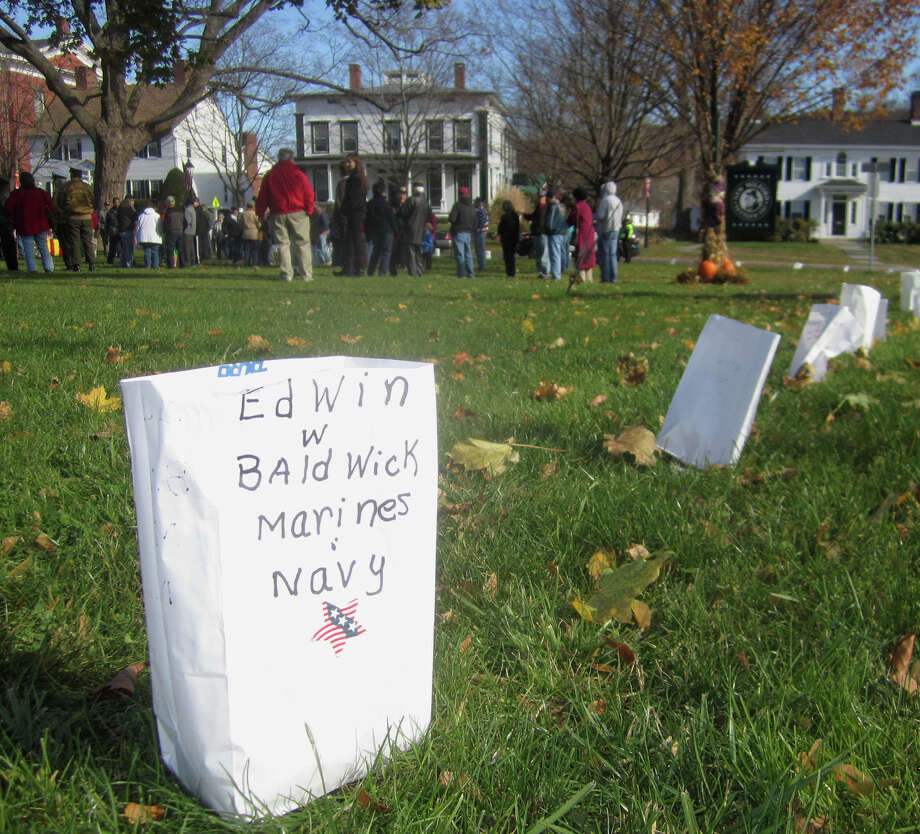 Luminaries dedicated to many of New Milford's veterans  line the periphery during New Milford's Veterans Day ceremony on the south end of the Village Green in New Milford. Nov. 11, 2013 Photo: Norm Cummings / The News-Times