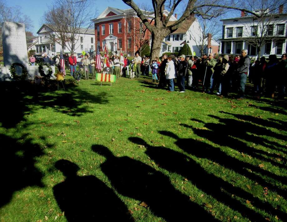 The honor guard casts a long yet welcome shadow across the grass near the town's war memorial during New Milford's Veterans Day ceremony on the south end of the Village Green in New Milford. Nov. 11, 2013 Photo: Norm Cummings / The News-Times