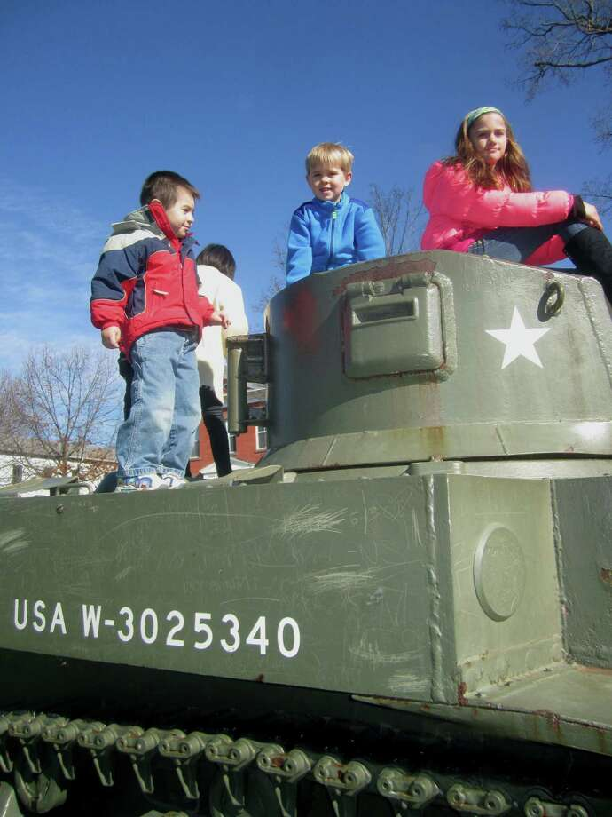 Youngsters seem to gravitate to the U.S. Army tank on the south end of the Village Green in New Milford whenever there is an event such as Monday's Veterans Day ceremony taking place nearby. Nov. 11, 2013 Photo: Norm Cummings / The News-Times