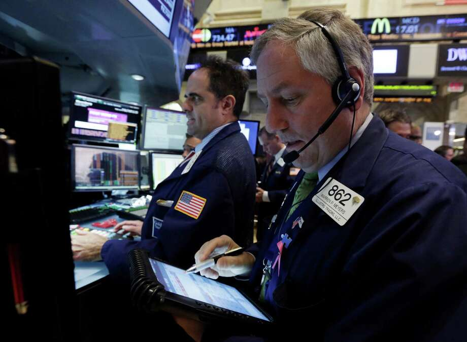 Trader Warren Meyers, right, works on the floor of the New York Stock Exchange Monday, Nov. 11, 2013. Investors this week will look for evidence that Americans are ready to start spending for the holidays. (AP Photo/Richard Drew) ORG XMIT: NYRD111 Photo: Richard Drew / AP