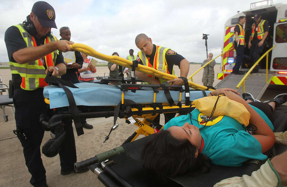 San Antonio Fire Department personnel prepare to transport a nursing student, playing the role of a mass casualty victim, into an emergency vehicle at  the San Antonio Mass Casualty Exercise Event in September. Photo: John Davenport / San Antonio Express-News
