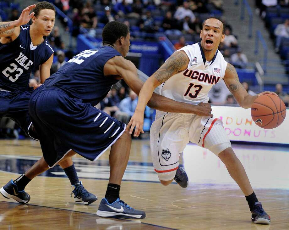Connecticut's Shabazz Napier (13) drives past Yale's Justin Sears (22) during the second half of an NCAA college basketball game, in  Hartford, Conn., on Monday, Nov. 11, 2013. Napier had a triple double and Sears a double double in Connecticut's 80-62 victory. Photo: Fred Beckham, AP / Associated Press