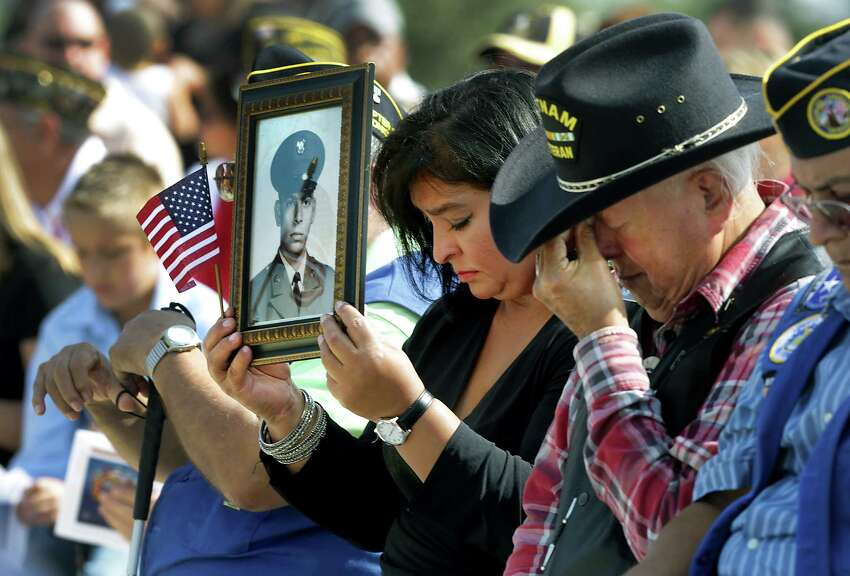 Maeria Becerra, left, holds a portrait of her father, Cesario Becerra who served in the Army, next to an emotional Sal Campos, right, who also served in the Army, as echoing taps are sounded at the Veterans Day Ceremony at Fort Sam Houston National Cemetery, Monday, Nov. 11, 2013.