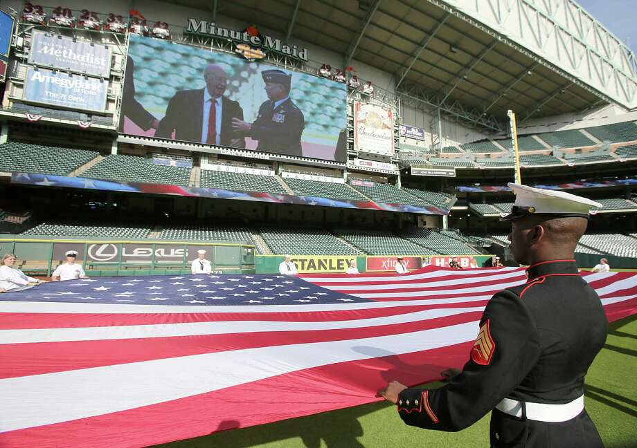 11/11/13: A marine holds an American Flag as Colonel George McDowell (ret) World War II veteran speaks at the Veterans Day -November 11, 2013, Salute to Veterans at Minute Maid Park in Houston, Texas.   at the Veterans Day -November 11, 2013, Salute to Veterans at Minute Maid Park in Houston, Texas. Photo: Thomas B. Shea, For The Chronicle / © 2013 Thomas B. Shea