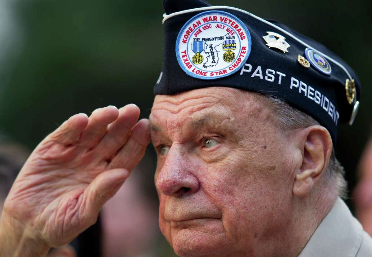 """Korean War Veteran Bob Mitchell gives a salute during the """"Houston Salutes American Heroes"""" celebration outside City Hall on Monday, Nov. 11, 2013, in Houston. The celebration included a Veterans job and health fair along with the annual parade that included dozens of local high school bands and organizations."""