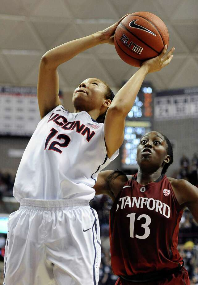Connecticut's Saniya Chong, left, shoots as Stanford's Chiney Ogwumike, right, defends during the second half of an NCAA college basketball game, Monday, Nov. 11, 2013, in Storrs, Conn. Connecticut won 76-57. Photo: Jessica Hill, AP / Associated Press