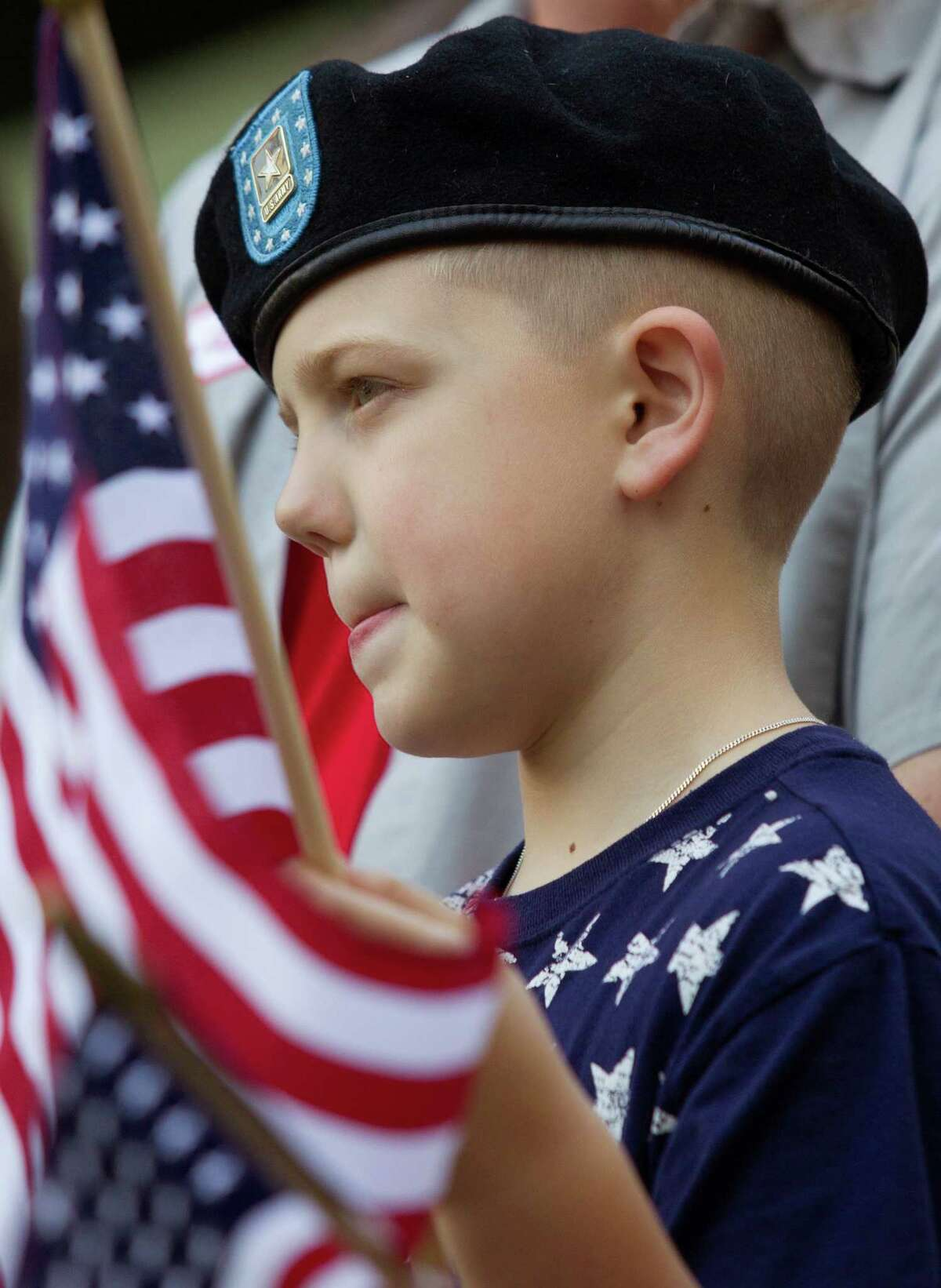 """Connor Price, 9, waves his American Flags during the """"Houston Salutes American Heroes"""" celebration outside City Hall on Monday, Nov. 11, 2013, in Houston. The celebration included a Veterans job and health fair along with the annual parade that included dozens of local high school bands and organizations."""