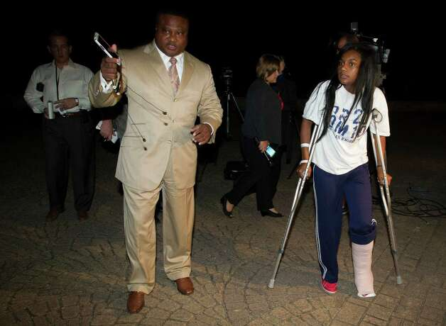 Quanell X walks with Brayiannia Young after a press conference outside Ben Taub hospital on Monday, Nov. 11, 2013, in Houston. Brayiannia was shot during a house party where two people were killed and 19 injured in the Cypress area on Saturday night.  Her brother, Willie Young, 21, was arrested and charged with deadly conduct  on Monday. A second suspect Randy Stewart, 18, was arrested and charged with aggravated assault.  She c