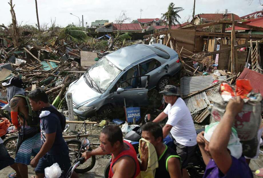 Survivors move past the damage caused by Typhoon Haiyan in Tacloban city, Leyte province, central Philippines on Monday, Nov. 11, 2013. The typhoon-ravaged Philippine islands faced an unimaginably huge relief effort that had barely begun Monday, as bloated bodies lay uncollected and uncounted in the streets and survivors pleaded for food, water and medicine. (AP Photo/Aaron Favila) ORG XMIT: XAF119 Photo: Aaron Favila / AP