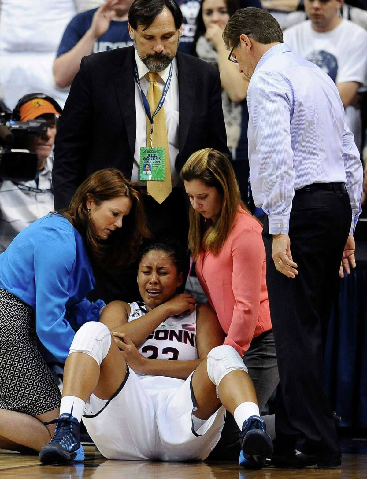 Connecticut head coach Geno Auriemma, right, looks at injured player Kaleena Mosqueda-Lewis, center, as she is tended to by assistant athletic trainer Rosemary Ragle, left, Team Physician Dr. Thomas Trojian, top center, and student athletic trainer Lauren Sheldon, second from right, during the second half of an NCAA college basketball game, Monday, Nov. 11, 2013, in Storrs, Conn. Mosqueda-Lewis left the game with an injury to her right elbow. Connecticut won 76-57.