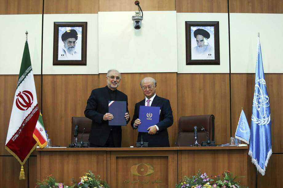 Head of Iran's Atomic Energy Organization Ali Akbar Salehi, left, and International Atomic Energy Agency (IAEA) Director General Yukiya Amano, pose for a photo under portraits of Iran's supreme leader, Ayatollah Ali Khamenei, left, and Iran's founder of Islamic Republic, Ayatollah Ruhollah Khomeini, right, following their meeting in Tehran, Iran, Monday, Nov. 11, 2013. Iran and the U.N. nuclear watchdog agency have reached a roadmap deal for cooperation during talks in Tehran Saturday that expands the monitoring of the country's nuclear sites. (AP Photo/ ISNA, Mehdi Ghasemi) ORG XMIT: ENO103 Photo: Mehdi Ghasemi / ISNA