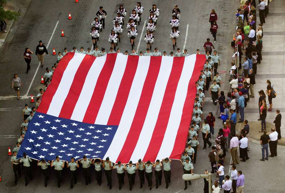 A large American Flag is marched down the streets of downtown during the annual City of Houston Veterans Day parade on Monday.  The celebration also included a Veterans job and health fair. Photo: J. Patric Schneider, Freelance / © 2013 Houston Chronicle