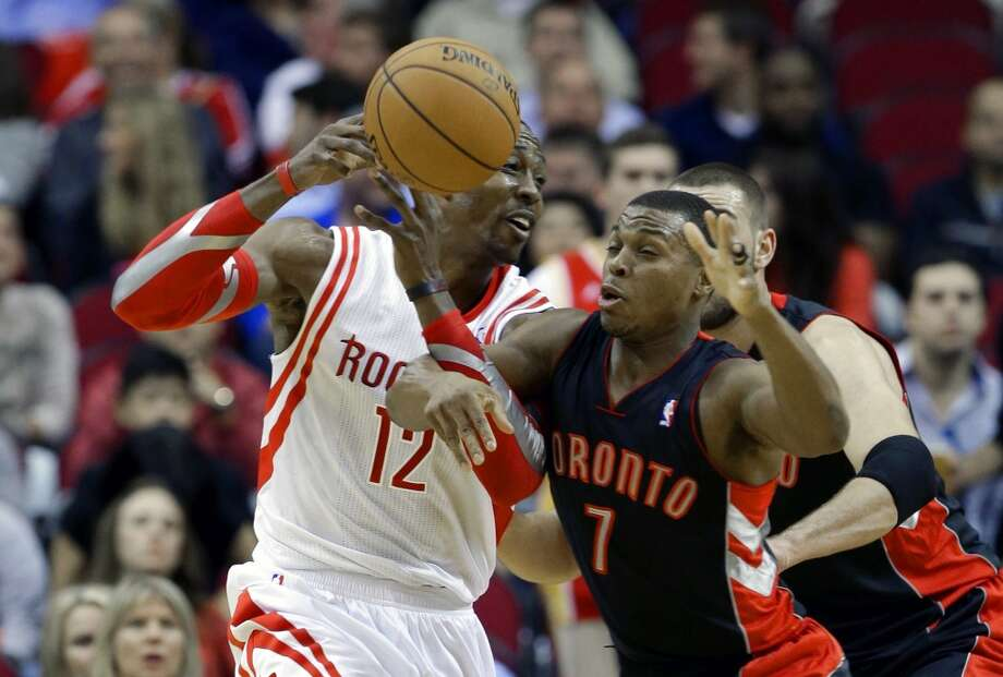 Rockets center Dwight Howard is defended by Raptors guard Kyle Lowry, a former Rocket. Photo: Scott Halleran, Getty Images