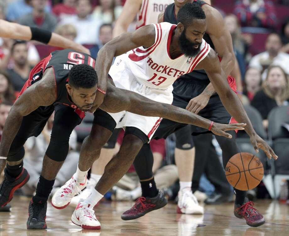 Rockets shooting guard James Harden tries to dribble around Amir Johnson of the Raptors. Photo: Scott Halleran, Getty Images