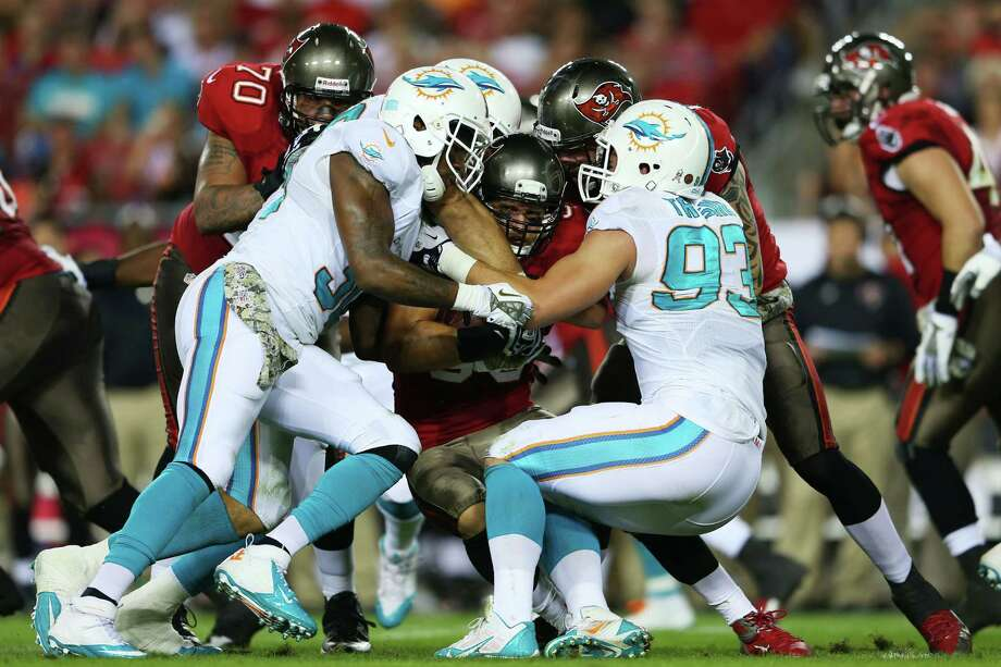 TAMPA, FL - NOVEMBER 11:  Brian Leonard #30 of the Tampa Bay Buccaneers is tackled by  Chris Clemons #30 and  Jason Trusnik #93 of the Miami Dolphins in the first half at Raymond James Stadium on November 11, 2013 in Tampa, Florida.  (Photo by Mike Ehrmann/Getty Images) ORG XMIT: 185380412 Photo: Mike Ehrmann / 2013 Getty Images