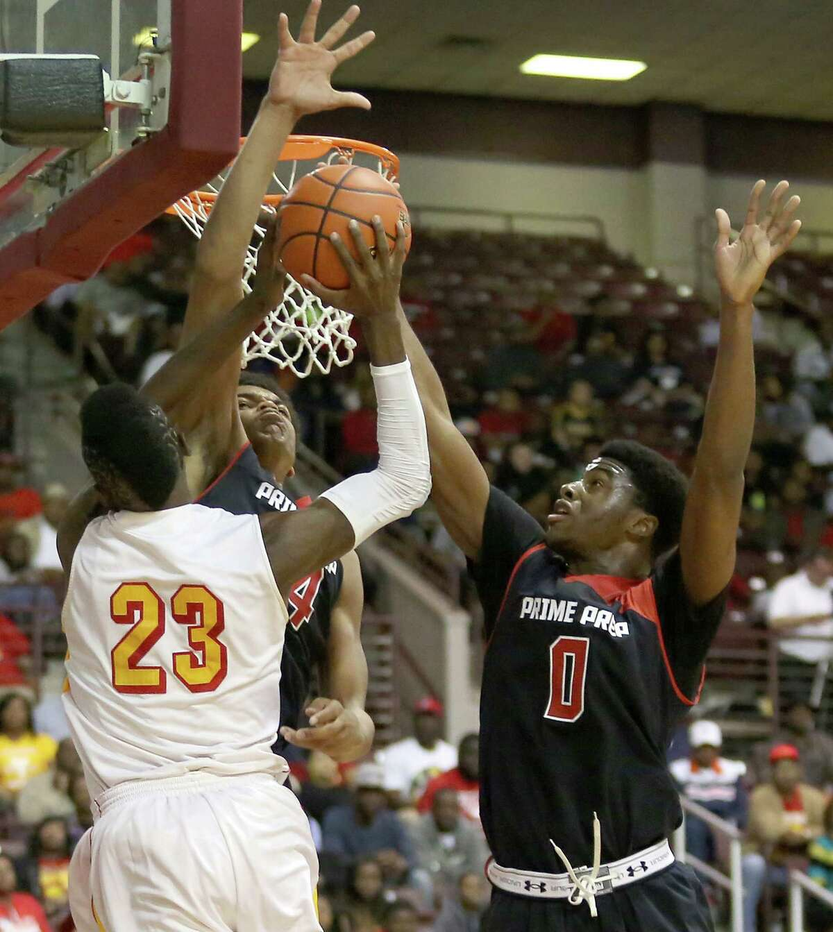 Yates' Melvin Swift (23) finds his path to the basket blocked by Dallas Prime Prep's Andrean Johnson and Emmanuel Mudiay (0) in Monday night's game.
