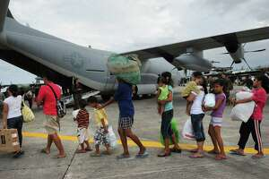 Survivors of Typhoon Haiyan in Tacloban, Philippines, line up to board a U.S. military cargo plane. Members of a Catholic church in San Antonio are in the planning stages of sending aid to victims of the disaster.