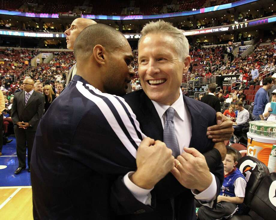 76ers coach Brett Brown (right), a former assistant to Gregg Popovich, gets a hug from Spurs guard Patty Mills. Photo: Charles Fox / Philadelphia Inquirer