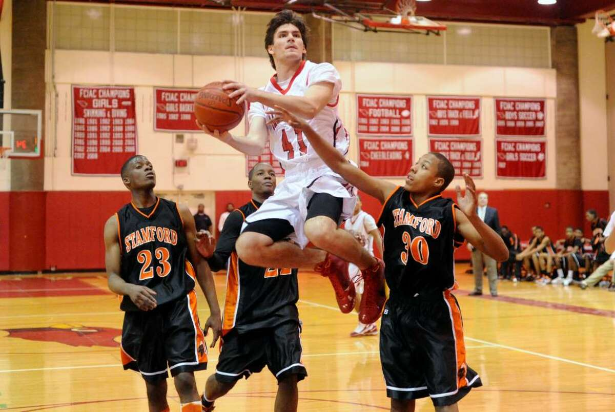 Greenwich's Greg Donlic hovers above the Stamford defense from left, Jethro Anilus, Mark Ellis and Barry Boderick as Greenwich High hosts Stamford High in a boys basketball game Friday night, January 29, 2010. Greenwich won the game 58-37.
