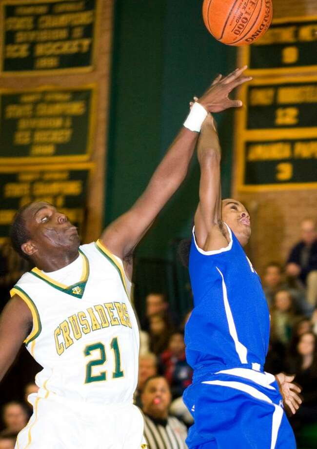 Trinity Catholic High School's #21 Aaron Spence, left, fights for the ball with Harding High School's #1 Romel Hendricks, right, during a boys basketball game in Stamford, CT on Jan. 29, 2010. Photo: Kerry Sherck / Stamford Advocate Freelance