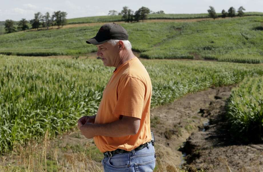"Wayne County board of supervisors member  Billy Joe Alley looks over an eroded cornfield that was recently converted from pasture to row crops near Lineville, Iowa. The once grassy, hilly landscape is made up of fragile soil that, unlike the rest of the state, is poorly suited for corn. ""They're raping the land,"" said Alley. Five million acres of conservation land has been converted to row crops since Obama's ethanol mandate, leading to erosion and pollution from fertilizer runoff. Photo: Charlie Riedel, AP"