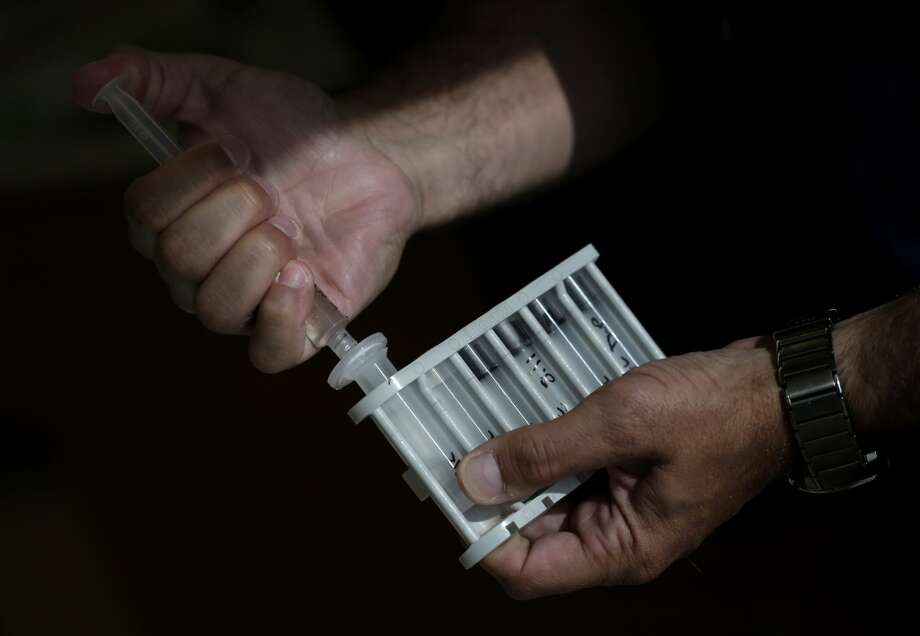 Des Moines water works lab supervisor Jeff Mitchell prepares a water sample for nitrate testing in Des Moines. A mandate to increase ethanol production has resulted in millions of acres of new row crops being planted, in some cases on highly erodible land, helping to increase nitrate pollution in municipal water supplies like Des Moines. Photo: Charlie Riedel, AP