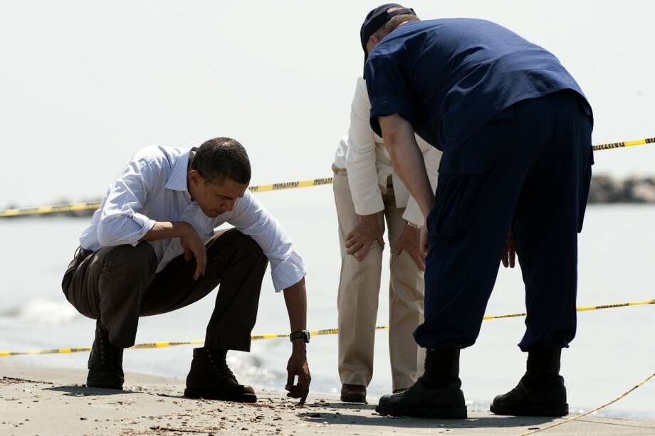U.S. President Barack Obama (left) looks at tar balls as he speaks with Coast Guard Commandant charged with overseeing the oil spill response Admiral Thad Allen (right) and LaFourche Parish President Charlotte Randolph (center) as they tour Port Fourchon Beach, Louisiana, on May 28, 2010 before a briefing on the federal government's response to the Gulf Coast oil spill.  Obama arrived in Louisiana to view the oil spill response amid suspense over the latest bid to cap the massive leak in the Gulf of Mexico. Photo: JIM WATSON, AFP/Getty Images