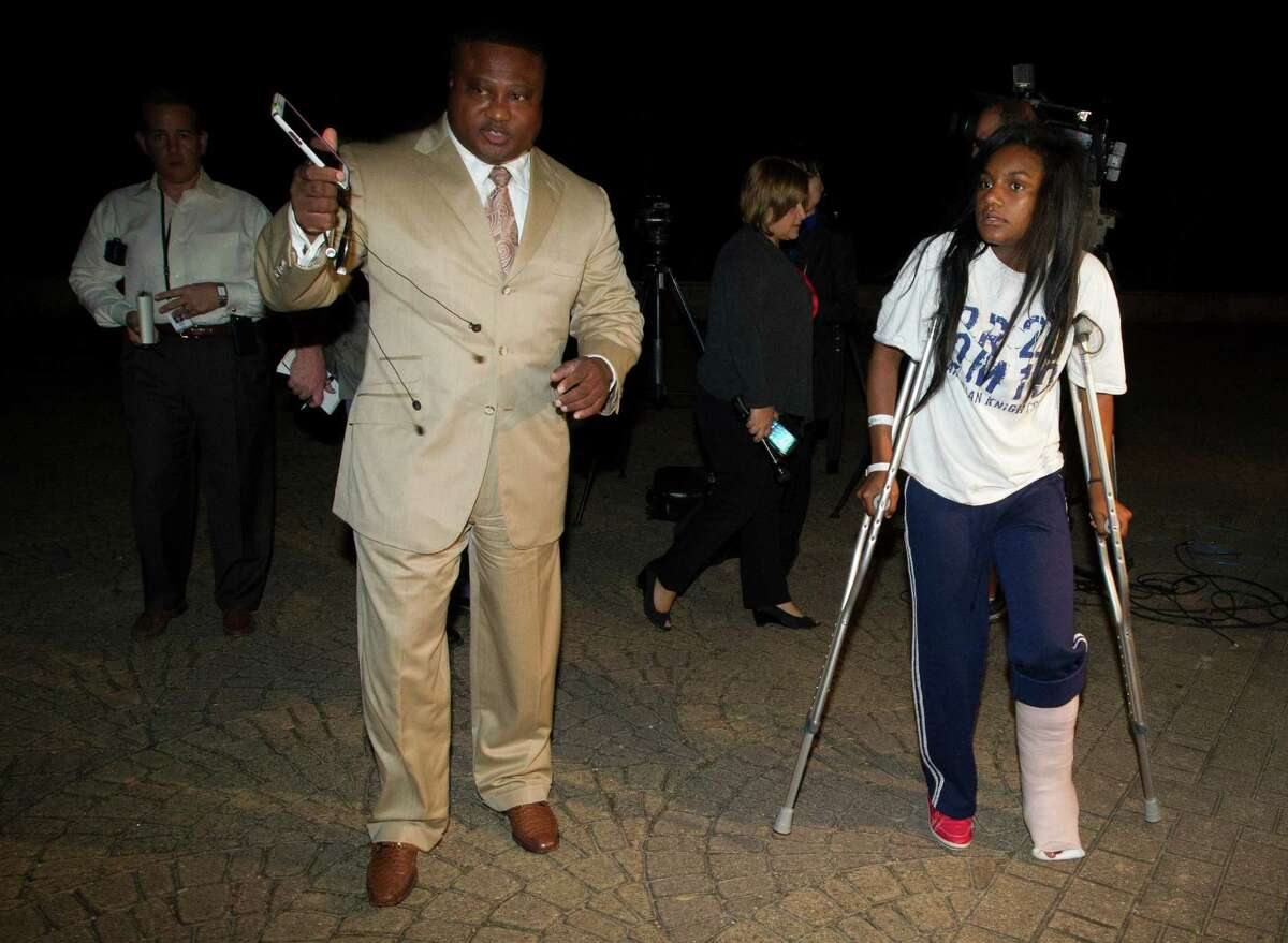 Quanell X walks with Brayiannia Young after a press conference outside Ben Taub hospital on Monday, Nov. 11, 2013, in Houston. Brayiannia was shot during a house party where two people were killed and 19 injured in the Cypress area on Saturday night. Her brother, Willie Young, 21, was arrested and charged with deadly conduct on Monday. A second suspect Randy Stewart, 18, was arrested and charged with aggravated assault. She claims her brother could not have done the shooting.